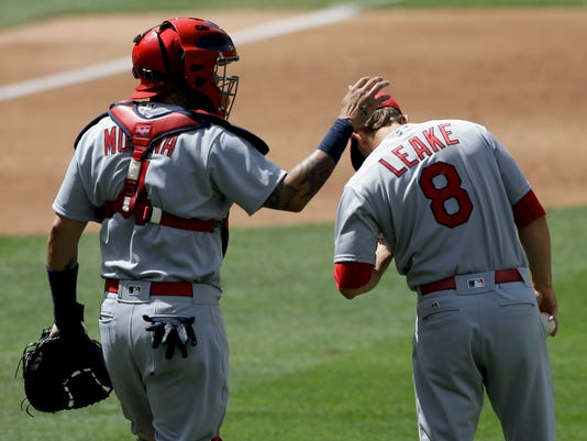 St. Louis Cardinals catcher Yadier Molina, left, pats starting pitcher Mike Leake as he has a word during the fourth inning of a baseball game against the San Diego Padres, Sunday, April 24, 2016, in San Diego. (AP Photo/Gregory Bull)
