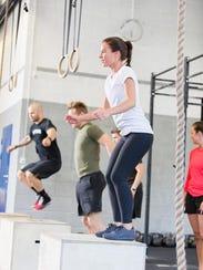 gym group trains box jumps