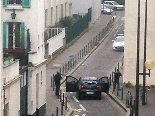 """Armed gunmen face police officers near the offices of the French satirical newspaper """"Charlie Hebdo"""" in Paris on Wednesday."""