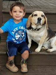 Kane Scott and the family dog pose for a photo.