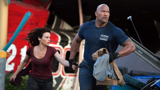 """Carla Gugino and Dwayne Johnson appear in a scene from """"San Andreas."""""""