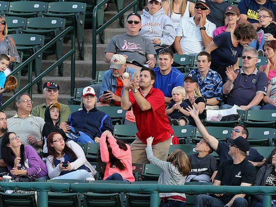 Some fans at Frontier Field protect themselves as others try to catch a foul ball.