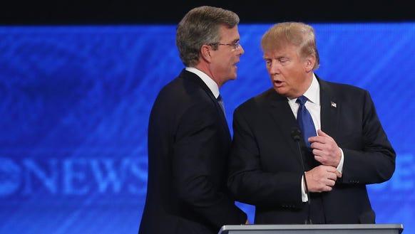 Republican presidential candidates Jeb Bush (L) and