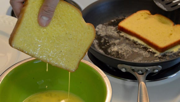 Egg and milk mixture drips off a piece of bread.