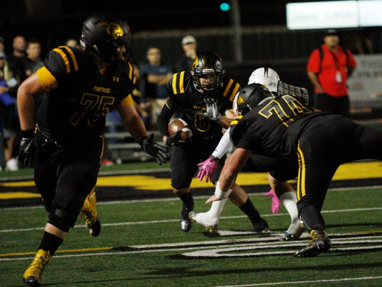 Newbury Park's  Ryan Matlock uses the help of his blockers to run the ball during Friday night's game at Calabasas.