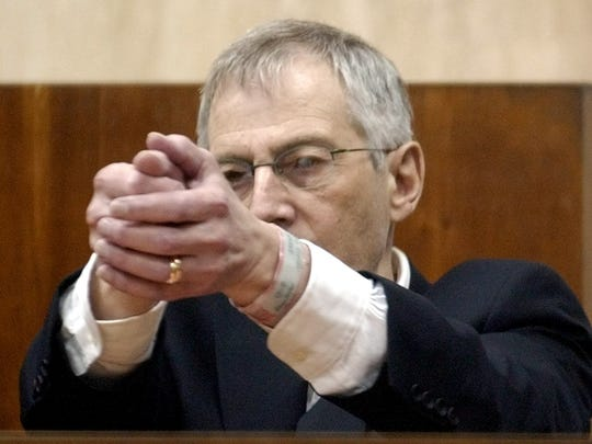 Robert Durst demonstrates how Morris Black handled a gun during testimony at his trial Thursday, Oct. 23, 2003, in Galveston, Texas.
