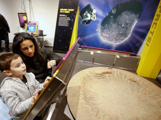 "Cecilia Welch of Landenberg, Pa., helps her son, Mason, 4, as they look at meteor impact results in front of a model of the Barringer Crater during the opening of the ""Great Balls of Fire"" exhibit at the Delaware Museum of Natural History. The exhibit examines the impact of asteroids, meteors and comets."