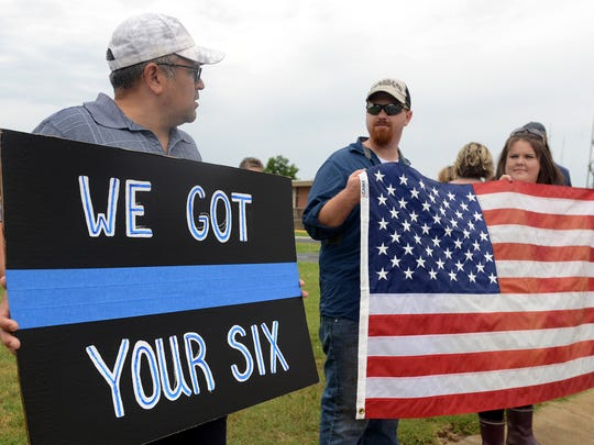 Jerome Bennavidez talks with Nathan Fuchs and Jessica Hulling during a gathering to support Jackson Police Department, Saturday morning.