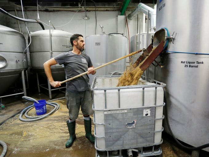 Head brewer Mike Booth pulls spent grain from a mash