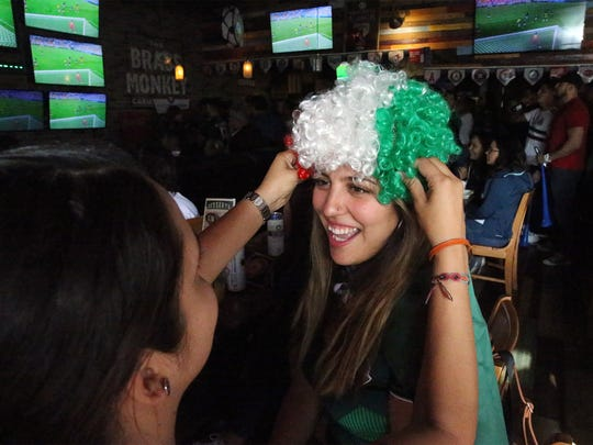 Mexico fan Mariel Cheda gets help with her tri-colored wig Monday at a Brass Monkey viewing party.