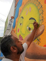Artist Rolando Siguenza paints a mural on the side of a building on Harrison Street at Ventura Avenue. Siguenza, who is from Oaxaca, Mexico, and designed the mural, collaborated with local artists MB Hanrahan and Uriel Leon on the mural.