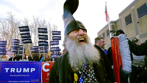 FILE - In this Tuesday, Feb. 9, 2016, file photo, satirical Democratic presidential candidate Vermin Supreme smiles while holding a giant toothbrush with a boot on his head during a campaign stop at a polling station on primary election day in Londonderry, N.H. The performance artist said he is mounting a write-in campaign as a Democrat candidate for the U.S. Senate in Massachusetts in the Tuesday, Sept. 1, 2020, primary election.