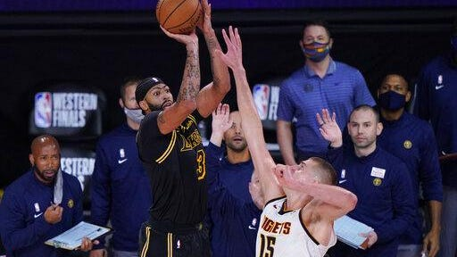 Los Angeles Lakers' Anthony Davis, left, shoots a 3-point basket over Denver's Nikola Jokic at the buzzer of an NBA conference final playoff basketball game Sunday in Lake Buena Vista, Fla. The Lakers won 105-103.