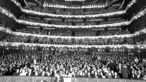 "Conductor Leonard Bernstein, standing lower center, shaking hands with unidentified member of orchestra as a full house audience settle into their seats for the opening performance of the season at New York?s Metropolitan Opera House, Sept. 19, 1972. Bernstein conducted the premier of a new production of Bizet's ""Carmen."""