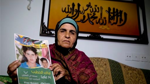 In this Tuesday, Jan. 27, 2015 photo, Palestinian Khawla Al-Khatib, holds a poster of her 14-year-old daughter Malak al-Khatib, detained in Israel, in the village of Beitin near the West Bank city of Ramallah.