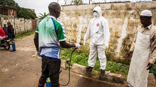 A health worker sprays disinfectant on a colleague who assisted with loading of a man suspected of suffering from the Ebola virus into an ambulance, in Freetown, Sierra Leone, on Wednesday, Sept. 24, 2014.  Freetown has seen a sharp increase in the number of people with the incurable, often-fatal virus.