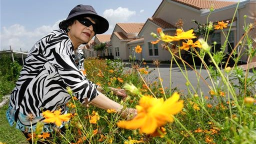 Geeta Chandran checks on the flowers in her garden at ShantiNiketan, a retirement community for people from India, in Tavares, Fla. ShantiNiketan is one of a growing number of niche retirement communities aimed at people of specific ethnic backgrounds, hobbies or collegiate allegiances.
