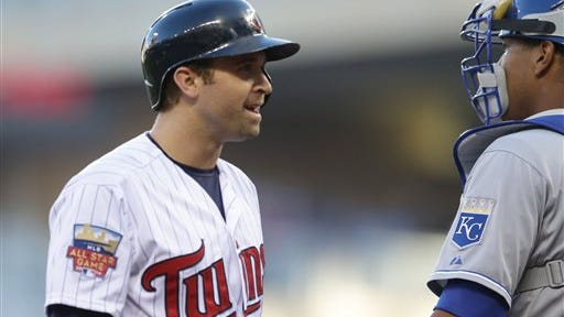 Minnesota Twins' Brian Dozier, left, looks past Kansas City Royals catcher Salvador Perez to have some words with plate umpire Corey Blaser after he was called out looking in the first inning of a baseball game Monday, June 30, 2014, in Minneapolis. (AP Photo/Jim Mone)