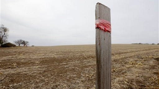 This March 17 file photo shows a stake in the ground wrapped with tape that marks the route of the Keystone XL pipeline in Tilden, Neb. The much-debated pipeline could produce four times more global warming pollution than the U.S. State Department has calculated, according to scientists at a Swedish research facility. They say the U.S. estimates didn?'t take into account that the added oil from the pipeline would drop prices by about $3 a barrel, spurring consumption that would then create more pollution.