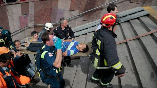 An injured man is carried out of a subway station after a rush-hour derailment in Moscow, Russia.