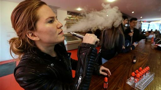 FILE - In this Feb. 20, 2014 photo, Talia Eisenberg, co-founder of the Henley Vaporium, uses her vaping device in New York. Under a New York City law taking effect Tuesday, April 29, 2014, vaporizing devices will be treated the same as a tobacco-based cigarette. The New York ban, along with similar measures in Chicago and Los Angeles and federal regulations proposed last week, are again igniting debate among public health officials, the e-cigarette industry and users lon the future of the popular devices.  (AP Photo/Frank Franklin II, File)