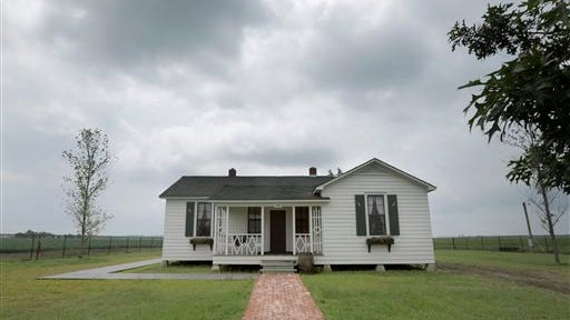 In this photo taken Friday, Aug. 8, 2014, rain clouds gather over the childhood home, dating to the mid 1930s, of singer Johnny Cash  in Dyess, Ark.