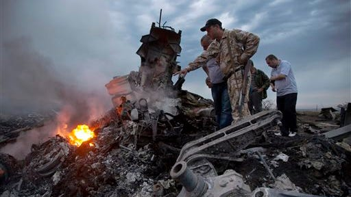 FILE - In this July 17, 2014 file photo, people inspect the crash site of a passenger plane near the village of Hrabove, Ukraine. The downing of the jet could prove to be a turning point in the country's conflict. But which way it turns depends mainly on who carried out the attack and how convincingly it can be proved to the world. (AP Photo/Dmitry Lovetsky)