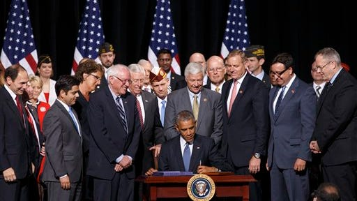 President Barack Obama signs into law the Veterans Access, Choice, and Accountability Act of 2014, a bill providing the Department of Veterans Affairs the resources to improve access and quality of care for veterans, Thursday, Aug. 7, 2014, at Fort Belvoir, Va. The legislation is a response to reports of veterans dying while awaiting appointments to see VA doctors and of a widespread practice of employees covering up months-long wait times for appointments. (AP Photo/J. Scott Applewhite)