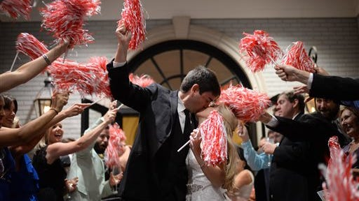 In this Aug. 9, 2014 handout photo, Wedding guests shake red-and-white pom-poms as University of Alabama football graduates Courtney and Scott Jenkins leave their wedding reception in Vestavia Hills, Ala. Like many other couples in states where college football is popular, the Jenkins incorporated a football theme and scheduled their wedding outside of football season to avoid the dilemma of planning around the game schedule. (AP Photo/Jennifer Oetting)  NO SALES