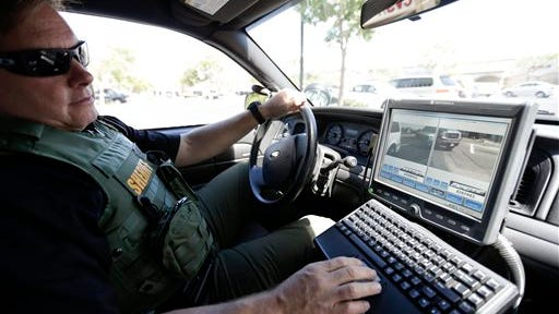 San Diego County Deputy Sheriff Ben Chassen looks at a monitor as his vehicle reads the license plates of cars in a parking lot Wednesday, Sept. 17, 2014, in San Marcos, Calif. A San Diego man is suing the San Diego Association of Governments for records collected on his vehicle by a plate-reader network that runs on information supplied by the San Diego Police Department, San Diego County Sheriff?s Department and eight other police departments. (AP Photo/Gregory Bull)