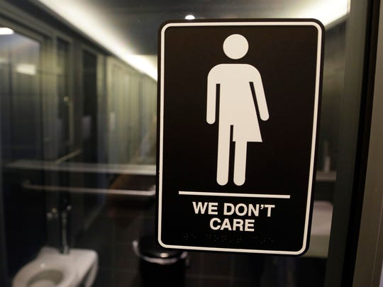 Signage hangs outside a restroom at 21c Museum Hotel