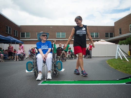 Resident Clara Riggs, left, shares a laugh with Kim King, director of therapeutic recreation, at the golf station during the Hanover Hall Summer Olympics on Wednesday in Hanover.