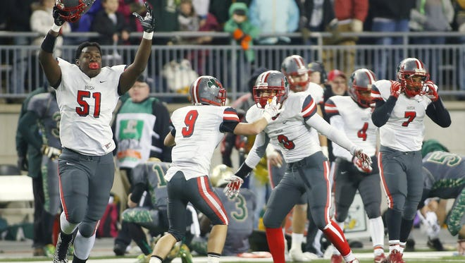 Toledo Central Catholics' James Hudson (51) and teammates celebrate the victory over Athens in the second half of a high school Div III championship football game, Thursday, Dec. 4, 2014, in Columbus, Ohio. Toledo won 56-52. (AP Photo/Mike Munden)