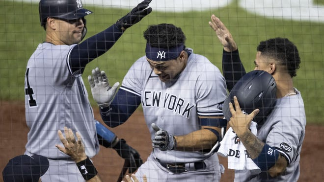 New York Yankees' Gary Sanchez, left, and Gleyber Torres, right, celebrate with Giancarlo Stanton, center, after Stanton's solo home run during the fourth inning of a game against the Washington Nationals on July 25 at Nationals Park in Washington.