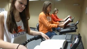 Students Sarah Limyansky, Jessica Cashman and Vanessa Macpherson (left to right) read while pedaling at FitDesks.