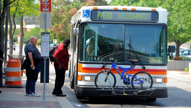 Riders enter a SMART bus at the Royal Oak Transit Center in Royal Oak.