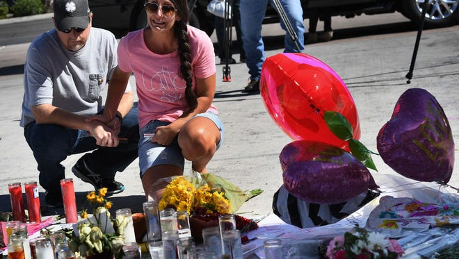 Jessica Yerkey (C) who attended the Route 91 country music festival reacts at a makeshift memorial on the Las Vegas Strip in Las Vegas, Nevada on October 3, 2017, after a gunman killed 59 people and wounded more than 500 others when he opened fire from the Mandalay Hotel on a country music festival. Police said the gunman, a 64-year-old local resident named as Stephen Paddock, had been killed after a SWAT team responded to reports of multiple gunfire from the 32nd floor of the Mandalay Bay, a hotel-casino next to the concert venue. / AFP PHOTO / Mark RALSTON        (Photo credit should read MARK RALSTON/AFP/Getty Images)