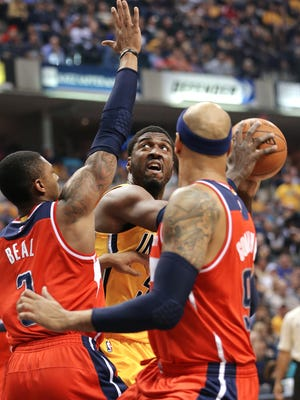 Indiana Pacers center Roy Hibbert looks to take a shot over Washington Wizards guard Bradley Beal  and forward Drew Gooden  in the first half of the game at Bankers Life Fieldhouse on Tuesday, April 14, 2015.