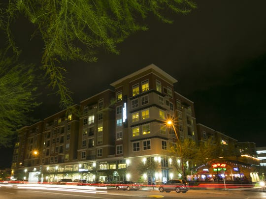 Cars pass by The District, an apartment complex across