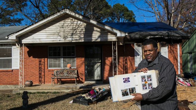 """January 3, 2018 - A day following a fire that destroyed his home, Derek Mosley, 57, holds one of the few items he and his loved ones were able to recover, a family photo album, in the 4200 block of Navaho Ave. on Wednesday. The house that the family had lived in since 1991 suffered $35,000 in damage and $4,000 in contents. According to a press release from the Memphis Fire Department, the """"origin and cause of the fire was determined to be a heating unit that malfunctioned in the hallway area. Mosley, a bishop at I Am Miracle Cogic, said he and his family were staying in a hotel at the time because their pipes burst Monday. On Tuesday, he received a call from his wife while she was working to deliver news their neighbors relayed to her: their house was engulfed in flames. """"My wife took it hard and my daughters took it hard. We had so many memories in our house. We don't have anything ... we do have Jesus,"""" Mosley said. """"It's a heartbreaking thing. We've been shown plenty love and I think that ought to be shown by people when people have lost everything in fires and floods and things that have been taken from them. I think that was beautiful - a lot of people showed us a lot of love."""""""