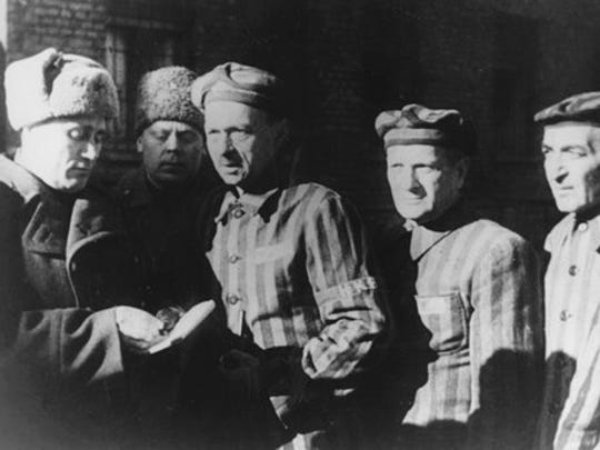 In this file photo dated January 1945, three Auschwitz prisoners, right, talk with Soviet soldiers after the Nazi concentration camp Auschwitz, in Poland, was liberated by the Russians. On Thursday, Jan. 22, 2015, Russia accused Poland of engaging in a mockery of history after the Polish foreign minister Grzegorz Schetyna credited Ukrainian soldiers, rather than the Soviet Red Army, with liberating Auschwitz 70 years ago. The latest exchange comes prior to the 70th anniversary of the liberation of Auschwitz by Soviet troops on Jan. 27, 1945, underlining deep tensions between Russia and Poland, which is hugely critical of Russia's recent actions in Ukraine.
