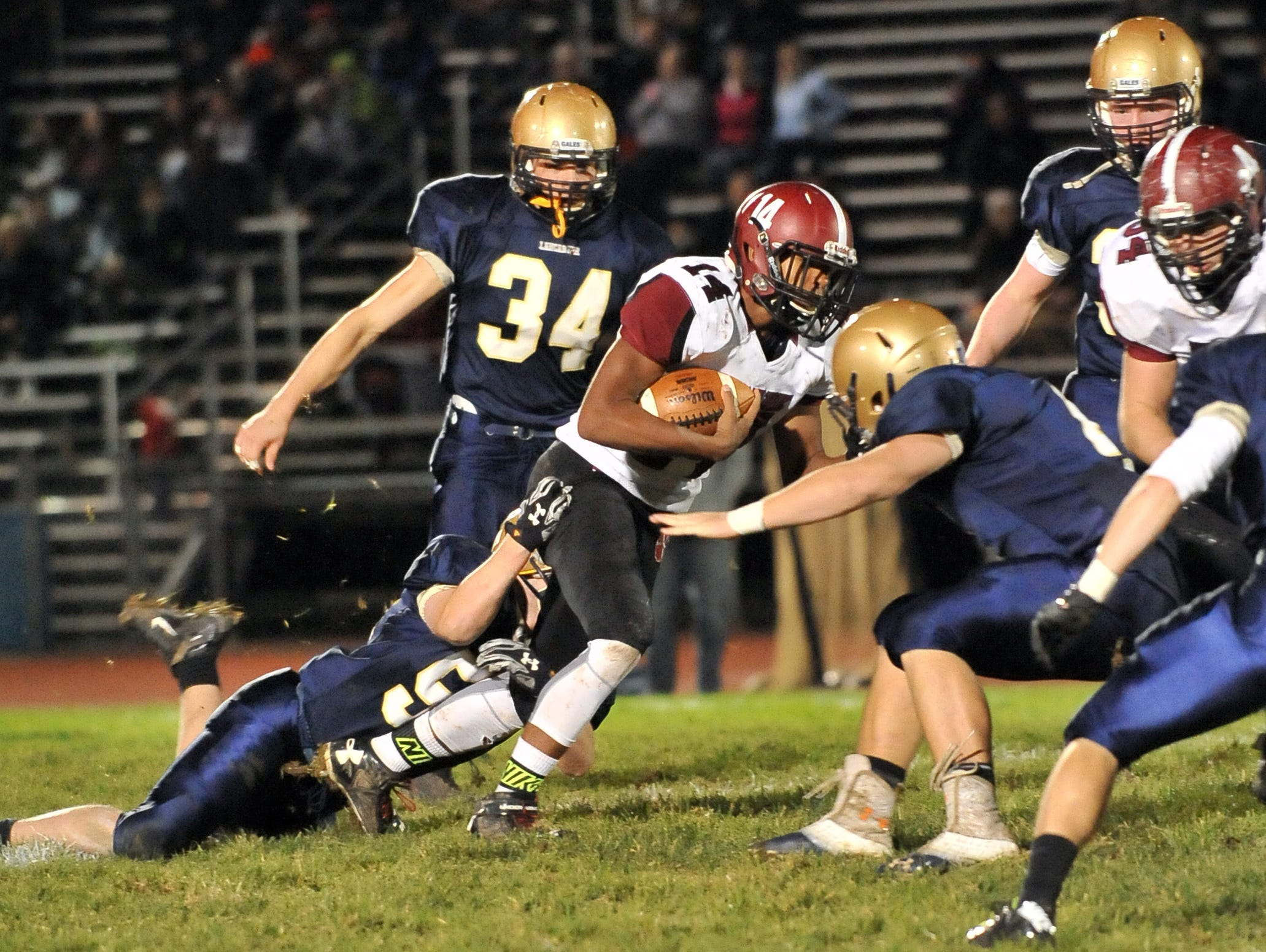 Newark's D'ante Woods is tackled by Lancaster's Ryan Roseberry during Friday night's game at Fulton Field in Lancaster. The Wildcats lost the game 38-7.