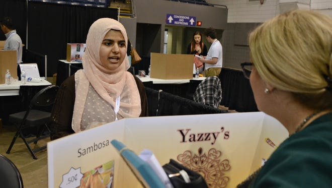 Coldwater High School student Yasmeen Alsuraimi, 17, explains the concept of her business, Yazzy's, Wednesday at the Generation E Institute's 12th Annual Student Business Showcase at Kellogg Arena in Battle Creek.