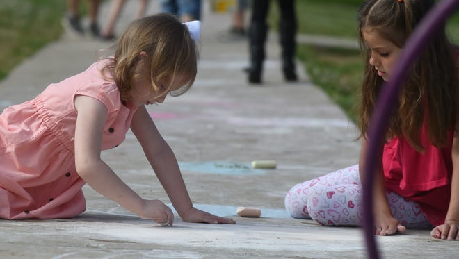 Two Mountain Home Kindergarten students draw on the sidewalk with chalk Wednesday, June 1, the last day of the school year.
