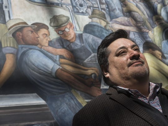 Detroit News reporter Louis Aguilar in front of the Diego Rivera frescos, top photo, at the Detroit Institute of Arts.