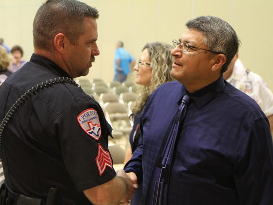 Sgt. Cory Moore shakes hands with Robert Martinez,