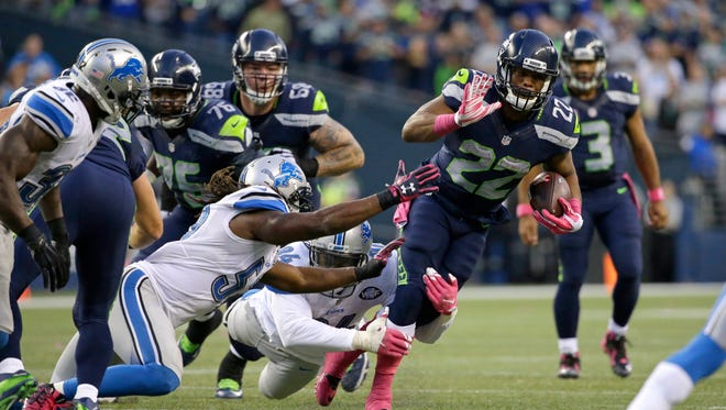 Seattle Seahawks running back Fred Jackson carries the ball as Detroit Lions defensive end Ezekiel Ansah (94) and Josh Bynes, lower center-left, attempt the tackle in the first half of an NFL football game, Monday, Oct. 5, 2015, in Seattle.