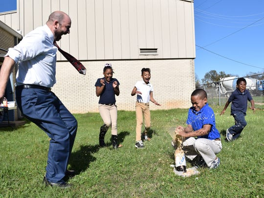 Arthur Joffrion (left), executive assistant superintendent of Rapides Parish schools, jumps back along with Z'Kiyah Patterson (second from left), Roye'l Roberts and James Harden as Hunter Jefferson puts Mentos candy in a two-liter bottle of diet soda during a science experiment Tuesday at Julius Patrick Elementary School. It was one of several electives offered to students with good behavior.