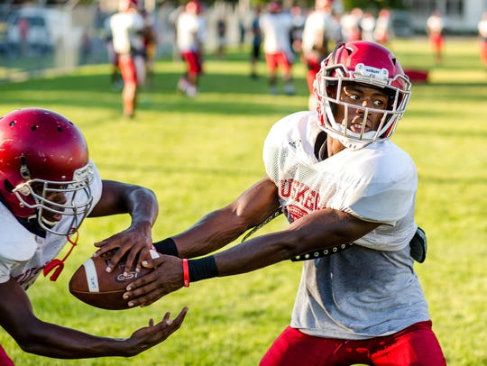 Muskegon quarterback Kalil Pimpleton, right, works