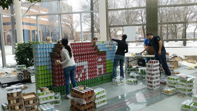 Members of the Wegmans Development Group build their Canstruction Rochester entry at Legacy Tower.